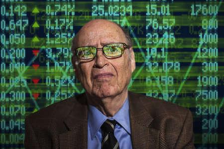 recuperating: Portrait of worried senior businessman in front of financial digital display