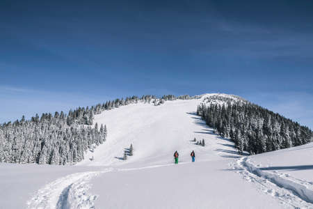 Distant view of two male skiers walking up snow covered mountain, Spitzingsee, Germany LANG_EVOIMAGES