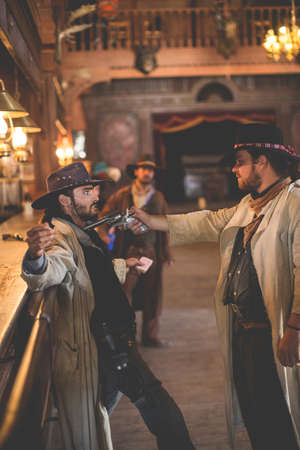 thespian: Cowboy aiming handgun in saloon on wild west film set, Fort Bravo, Tabernas, Almeria, Spain