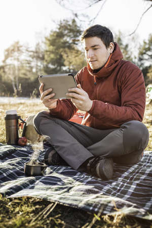 Young man sitting on picnic blanket in forest looking at digital tablet