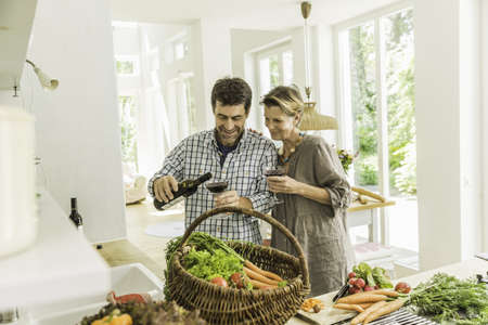 drinks after work: Couple pouring red wine whilst preparing fresh vegetables LANG_EVOIMAGES