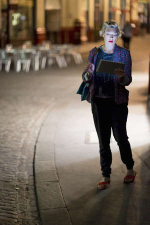 Mature woman using digital tablet on the street at night, London, UK