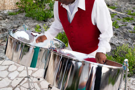 Mature man playing steel drums, mid section