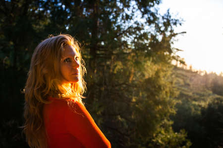 Mid adult woman looking over her shoulder in mountain forest at sunset, Palomar, California, USA
