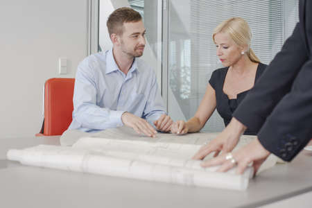 Colleagues discussing blueprints in office LANG_EVOIMAGES