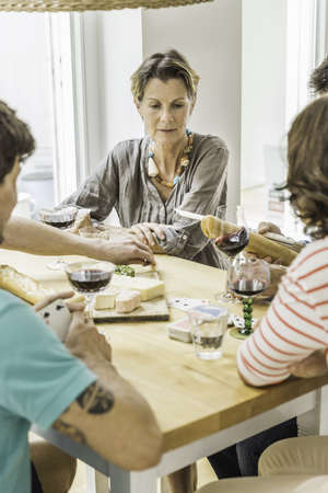 say cheese: Adult friends playing cards and drinking wine at dining table LANG_EVOIMAGES