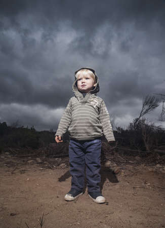 environmental issues: Young boy standing against stormy sky