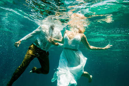 jamaican man: Couple in wedding attire, holding hands, underwater