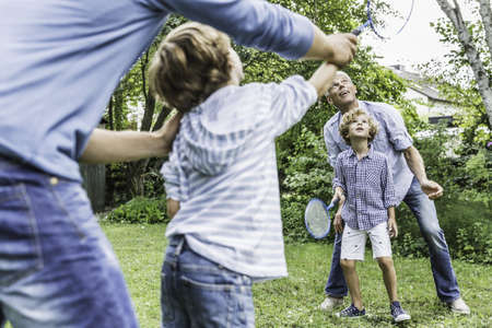 Mature man and son playing badminton with grandsons in garden