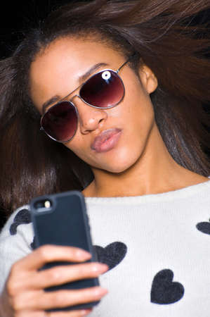 puckered lips: Portrait of young woman wearing sunglasses, taking self portrait using smartphone