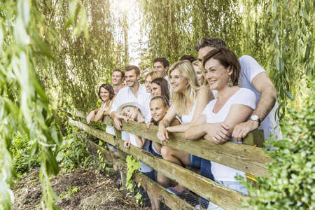50 54 years: Portrait of group of people leaning against fence in forest