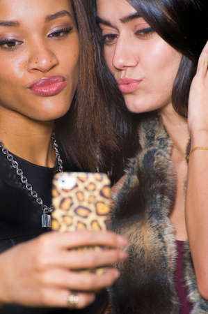 puckered lips: Two young women pouting at smartphone