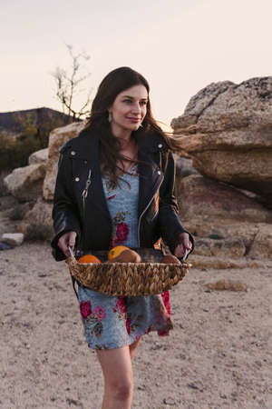 Young woman carrying basket of fruit for picnic in desert, Los Angeles, California, USA LANG_EVOIMAGES