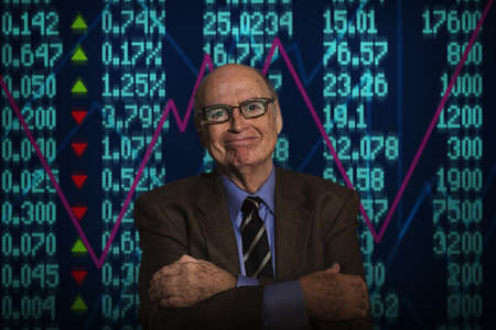 numeric: Portrait of senior businessman smiling in front of financial digital display