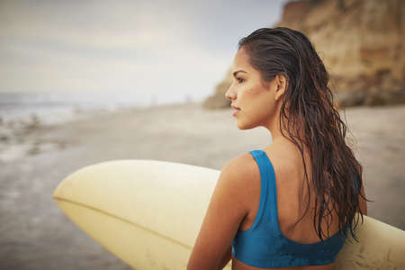 Rear view of young woman carrying surfboard on beach, San Diego, California, USA