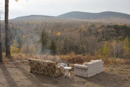 out of context: Two sofas and campfire with autumn forest view, Maine, USA LANG_EVOIMAGES