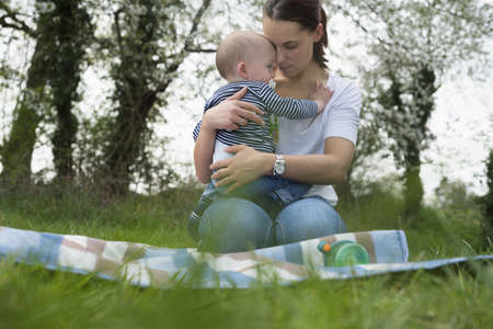 casual clothing 12 year old: Young mother hugging baby son on picnic blanket in field