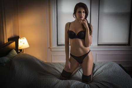 nightstands: Woman in lingerie kneeling on bed LANG_EVOIMAGES