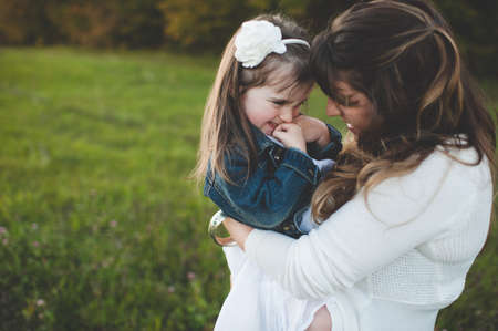 alice band: Mother holding young daughter, outdoors