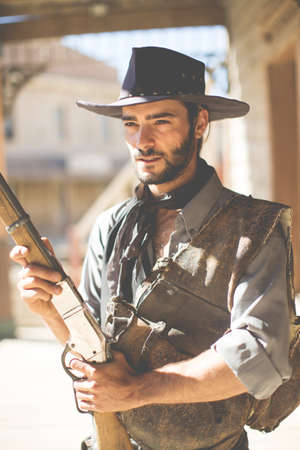 Cowboy holding up shotgun on wild west film set, Fort Bravo, Tabernas, Almeria, Spain