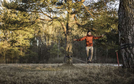 sweatshirts: Young man balancing on slackline in forest LANG_EVOIMAGES