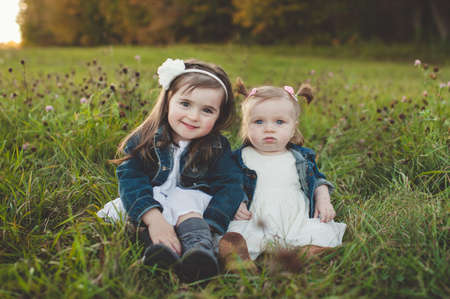 alice band: Portrait of young girl and baby sister in field LANG_EVOIMAGES