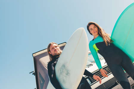 Portrait of couple holding surfboards, low angle view