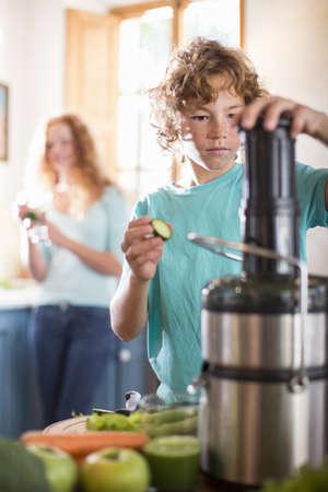 Teenage boy blending fruit in kitchen