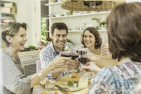 say cheese: Adult friends making a toast with red wine at dining table
