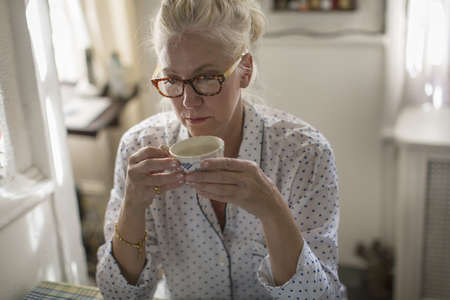 Sad mature woman sitting at breakfast table with teacup LANG_EVOIMAGES