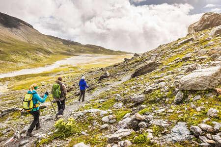 above 18: Male and female hikers hiking along path, Fil de Cassons, Segnesboden, Graubunden, Switzerland