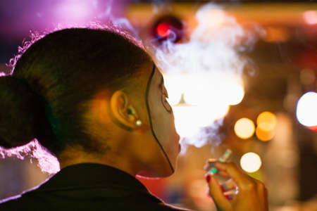 entertaining area: Rear view of young woman in nightclub smoking cigarette