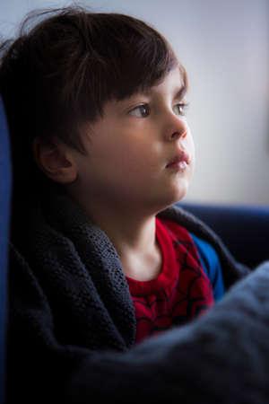 pyjama: Close up portrait of boy wrapped in blanket on sofa LANG_EVOIMAGES