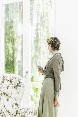 Portrait of senior woman looking out of window in living room LANG_EVOIMAGES