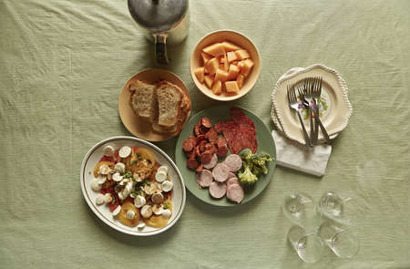 Overhead view of plates of food on tablecloth