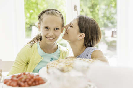 Young woman whispering to daughter at birthday party LANG_EVOIMAGES