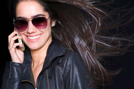 Portrait of young woman wearing sunglasses, taking on smartphone