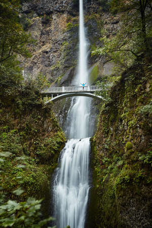 Male hiker crossing footbridge over Multnomah Falls, Oregon, USA LANG_EVOIMAGES