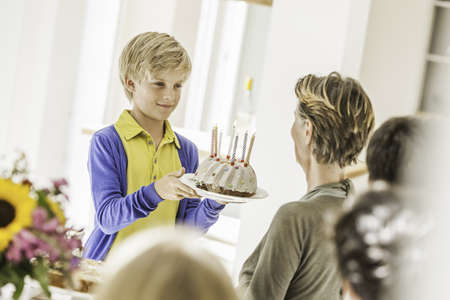 give out: Boy handing grandmother birthday cake at party in dining room