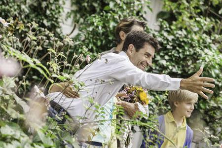 Mature couple greeting grandchildren in garden LANG_EVOIMAGES