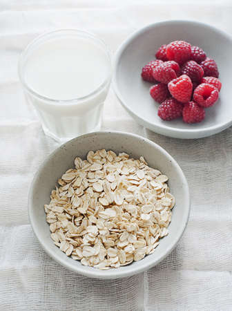 Bowl of oatmeal with raspberries and a cup of milk