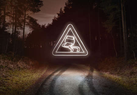 no skid: Tyre skid marks and glowing slippery warning sign above forest road at night
