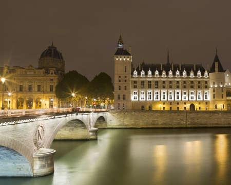 View of floodlit Musee de la Conciergerie and Pont au change at night, Paris, France