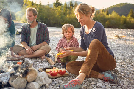 Boy sitting next to campfire watching mature woman prepare food LANG_EVOIMAGES
