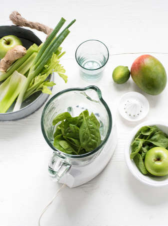 Blender with fresh green fruits and vegetables