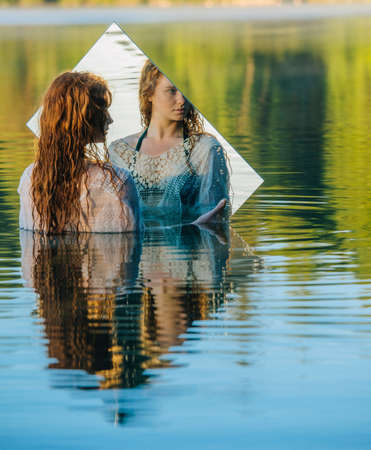 reflective: Young woman standing in lake, holding mirror, looking at reflection