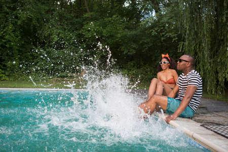 Couple splashing legs in pool