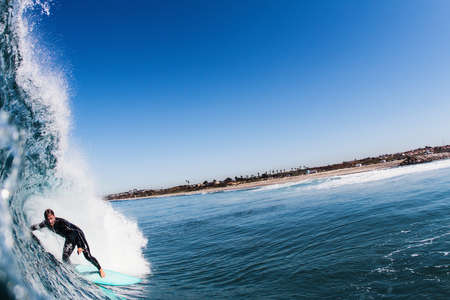 Close up of ocean wave and mid adult man surfing, Carlsbad, California, USA