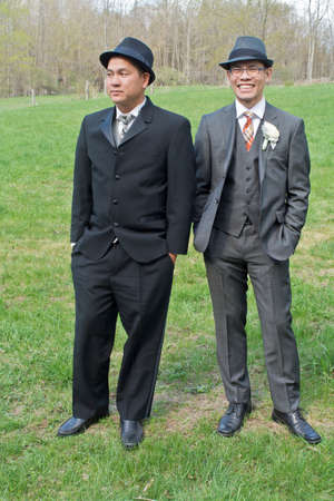 Portrait of two male wedding guests, wearing suits, standing in filed LANG_EVOIMAGES