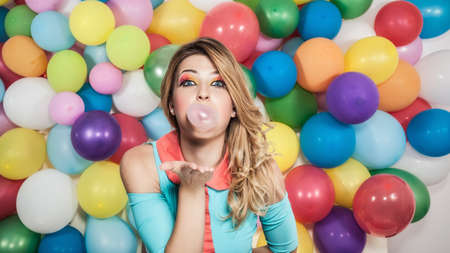 gumballs: Young woman standing in front of colourful balloons, blowing bubble with bubblegum LANG_EVOIMAGES
